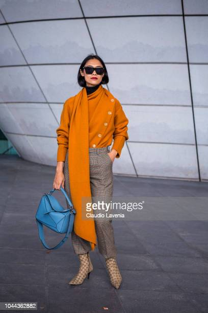 A guest wearing an orange sweater checked pants blue Loewe bag and Gucci boots is seen after the Giambattista Valli show on October 1 2018 in Paris...