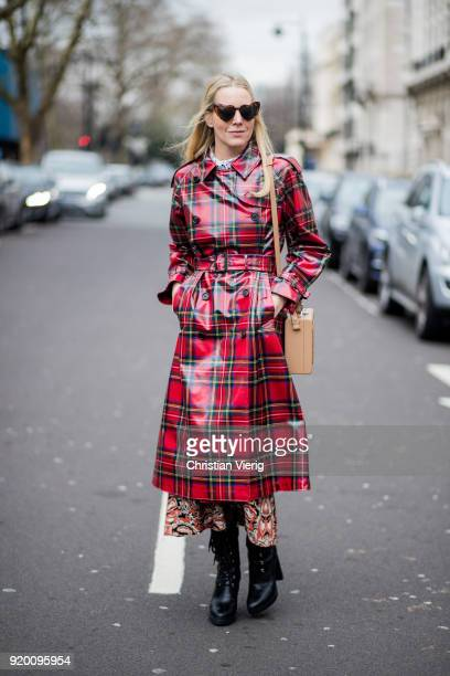 A guest wearing bag with print repetition creates change and tartan Burberry coat seen outside Delpozo during London Fashion Week February 2018 on...