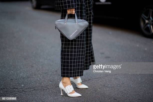 A guest wearing Balenciaga bag checked suit white heels is seen outside Max Mara during Milan Fashion Week Spring/Summer 2018 on September 21 2017 in...