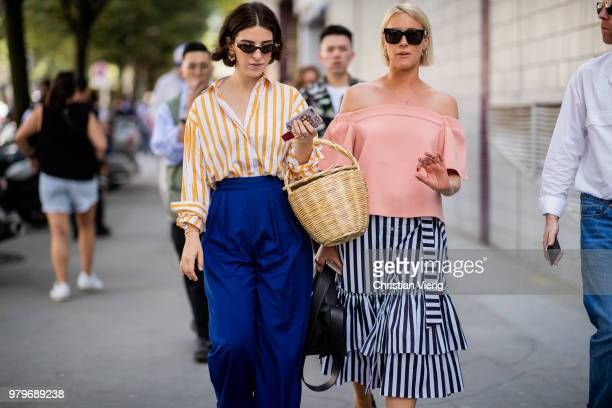 A guest wearing basket bag high waisted blue pants striped button shirt and a guest wearing salmon colored off shoulder top striped skirt is seen...