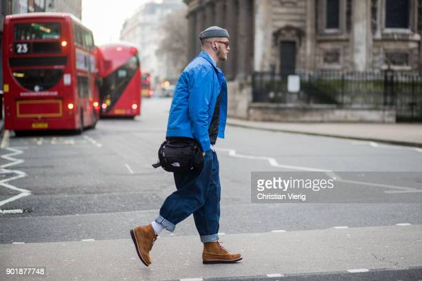 A guest wearing beanie baggy jeans blue jacket The North Face bag during London Fashion Week Men's January 2018 on January 6 2018 in London England