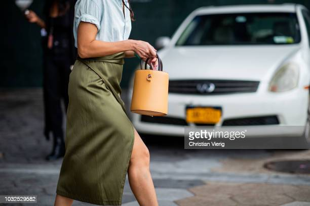 A guest wearing beige bag olive green silk skirt with slit blue blouse is seen outside Michael Kors during New York Fashion Week Spring/Summer 2019...