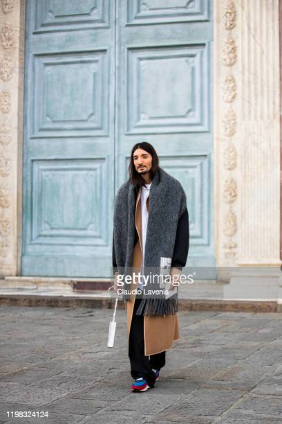 A guest wearing beige coat black bomber and grey long scarf is seen before Jil Sander show at Piazza Santa Maria Novella on January 08 2020 in...