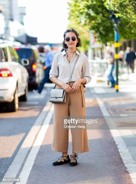 A guest wearing beige cropped pants blouse silver bag outside Busnel on August 30 2017 in Stockholm Sweden