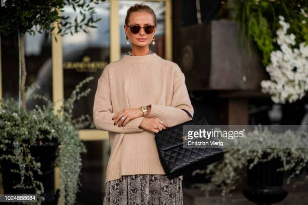 A guest wearing beige knit black Chanel bag is seen during Stockholm Runway SS19 on August 28 2018 in Stockholm Sweden