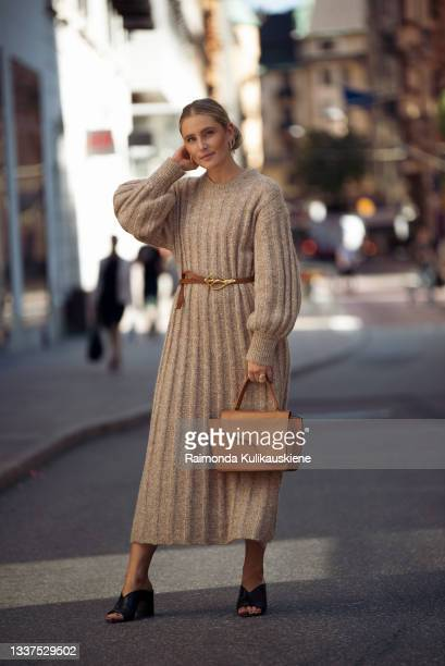 Guest wearing beige knitted long dress, light brown bag and black high heels during Stockholm fashion week Spring/Summer 2022 on August 31, 2021 in...