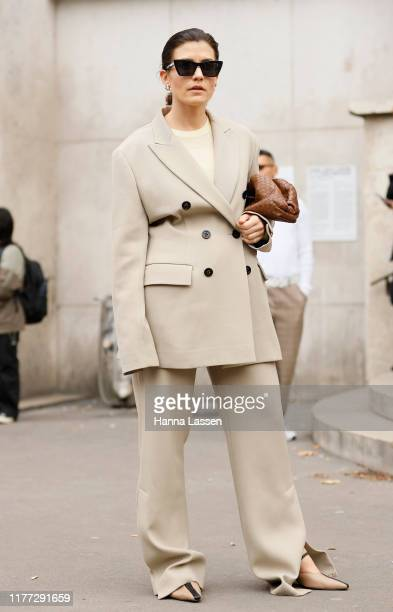 A guest wearing beige oversized suit and Bottega Veneta clutch outside Rick Owens during Paris Fashion Week Womenswear Spring Summer 2020 on...