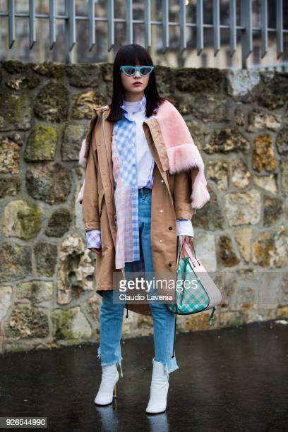 A guest wearing beige parka white heels boots and checked bag is seen in the streets of Paris before the Loewe show during Paris Fashion Week...