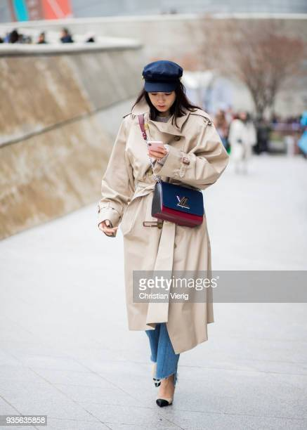A guest wearing beige trench coat Louis Vuitton bag flat cap denim jeans Chanel shoes is seen at the Hera Seoul Fashion Week 2018 F/W at Dongdaemun...