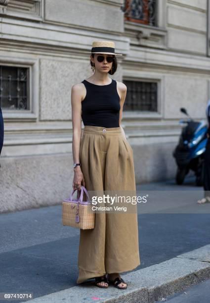 A guest wearing beige wide leg pants black top straw hat Prada bag is seen outside Salvatore Ferragamo during Milan Men's Fashion Week Spring/Summer...