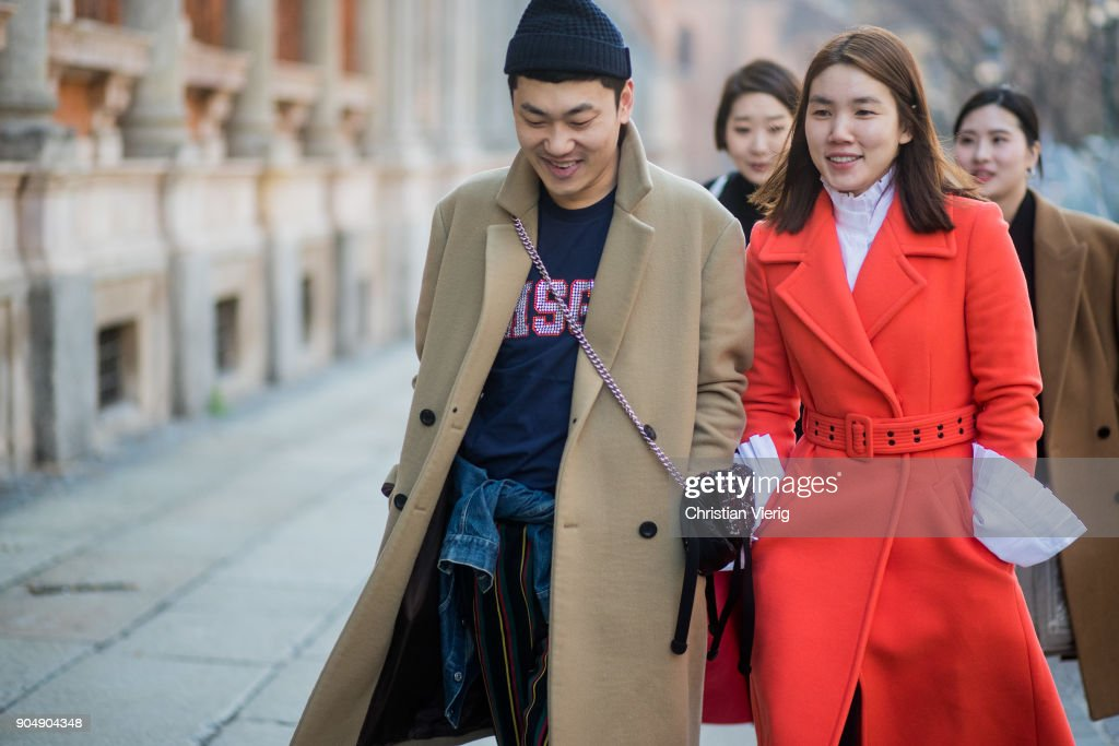 A guest wearing beige wool coat and a guest wearing red wool coat is seen outside MSGM during Milan Men's Fashion Week Fall/Winter 2018/19 on January 14, 2018 in Milan, Italy.