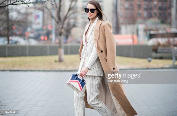 A guest wearing beige wool coat white striped suit seen outside Dion Lee on February 10 2018 in New York City