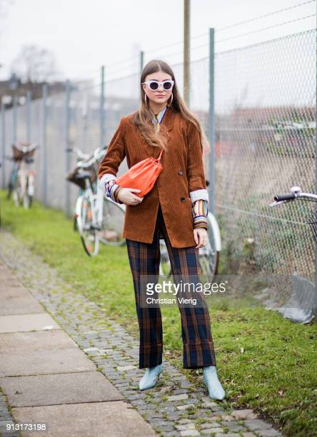 A guest wearing belt bag checked flared pants outside Munthe during the Copenhagen Fashion Week Autumn/Winter 18 on February 1 2018 in Copenhagen...