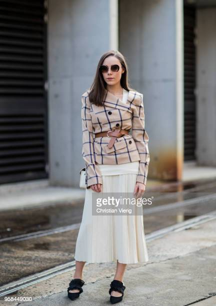 A guest wearing belted checked blazer jacket midi skirt during MercedesBenz Fashion Week Resort 19 Collections at Carriageworks on May 14 2018 in...