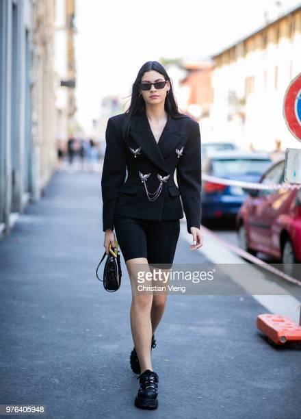 A guest wearing bike pants black blazer jacket is seen outside M1992 during Milan Men's Fashion Week Spring/Summer 2019 on June 16 2018 in Milan Italy
