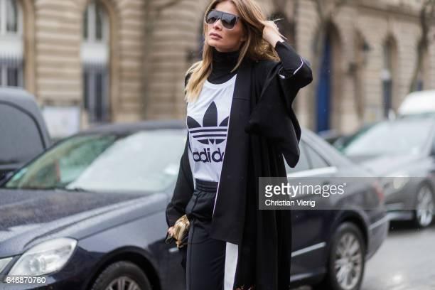 A guest wearing black Adidas track suit pants Adidas white tshirt kimono outside Lanvinon March 1 2017 in Paris France
