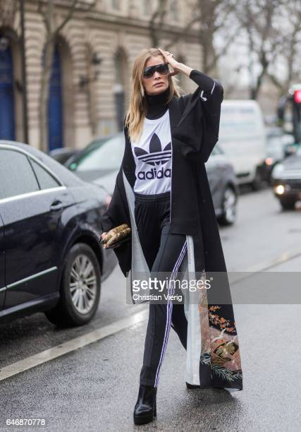 A guest wearing black Adidas track suit pants Adidas white tshirt kimono outside Lanvinon March 1 2017 in Paris France