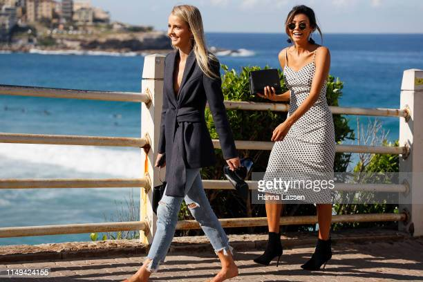 A guest wearing black and white midi dress and ankle boots at MercedesBenz Fashion Week Resort 20 Collections on May 16 2019 in Sydney Australia