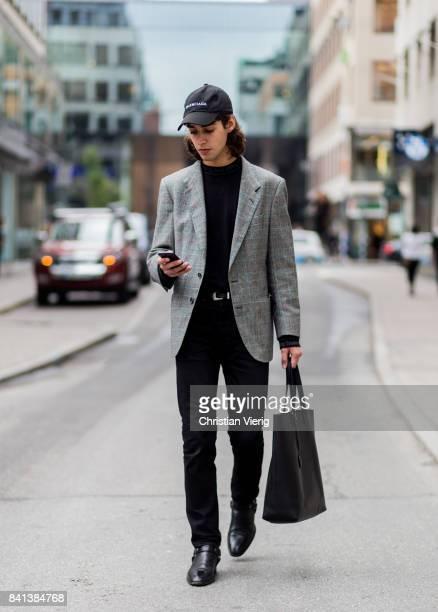 A guest wearing black bag Balenciaga cap boots black jeans grey blazer jacket on August 31 2017 in Stockholm Sweden