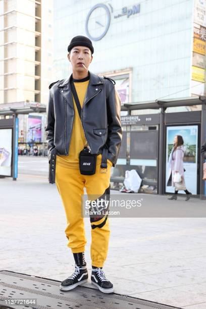 Guest wearing black beanie black rider jacket yellow training suit and Vans sneakers is seen at the Hera Seoul Fashion Week 2019 F/W at Dongdaemun...