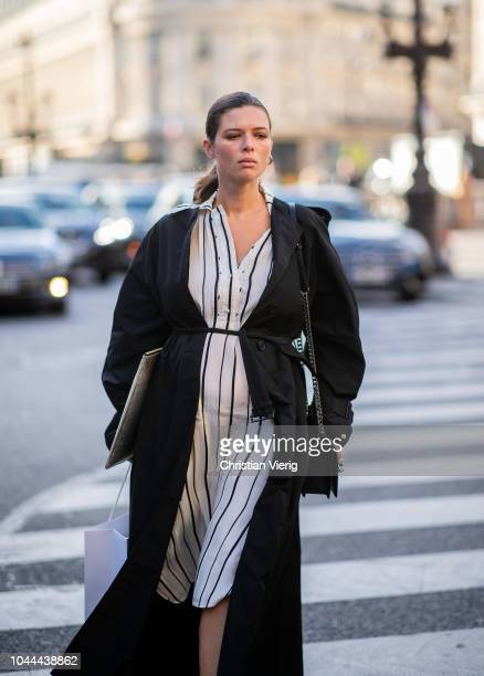 A guest wearing black belted coat white black striped dress is seen outside Stella McCartney during Paris Fashion Week Womenswear Spring/Summer 2019...