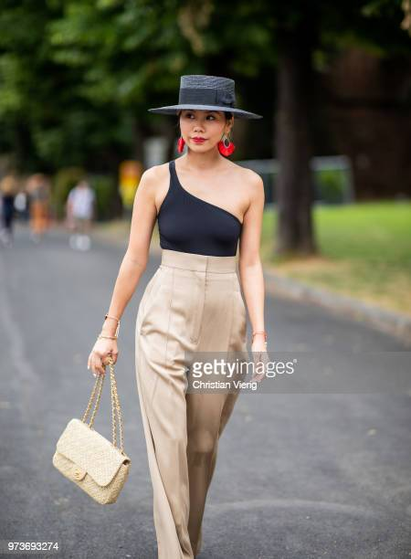 A guest wearing black body beige high waisted pants Chanel bag and shoes hat red earrings is seen during the 94th Pitti Immagine Uomo on June 13 2018...