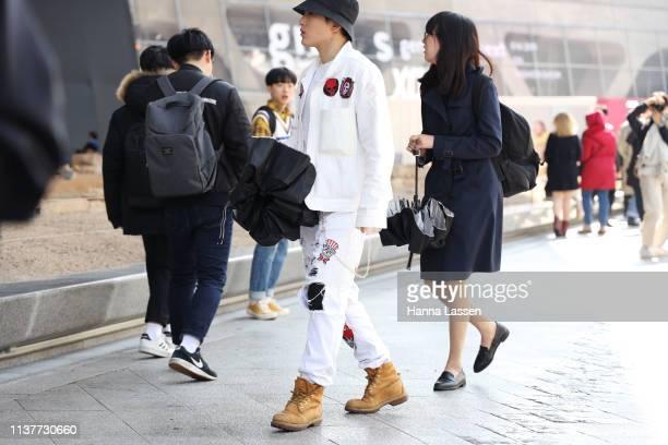 Guest wearing black bucket hat white denim jacket and jeans is seen at the Hera Seoul Fashion Week 2019 F/W at Dongdaemun Design Plaza at Dongdaemun...