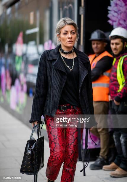 A guest wearing black corduroy jacket red snake print pants is seen outside Natasha Zinko during London Fashion Week September 2018 on September 18...