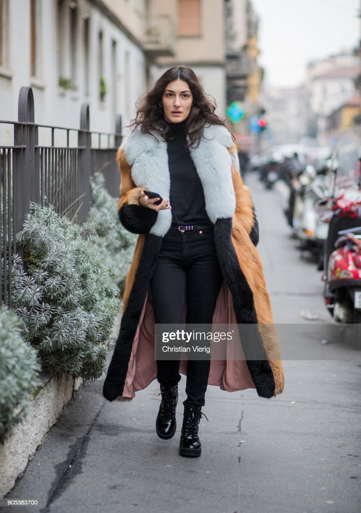 A guest wearing black denim jeans, fur coat is seen outside No21 during Milan Men's Fashion Week Fall/Winter 2018/19 on January 15, 2018 in Milan, Italy.
