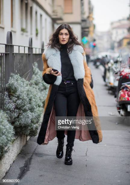 A guest wearing black denim jeans fur coat is seen outside No21 during Milan Men's Fashion Week Fall/Winter 2018/19 on January 15 2018 in Milan Italy