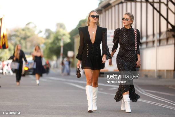 Guest wearing black dress, white leather boots and Bally bag at Mercedes-Benz Fashion Week Resort 20 Collections on May 15, 2019 in Sydney, Australia.