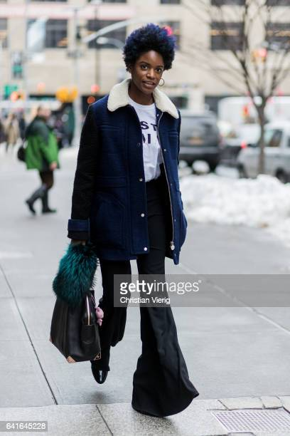 A guest wearing black flared pants wool coat white tshirt outside Creatures of the Wind on February 11 2017 in New York City