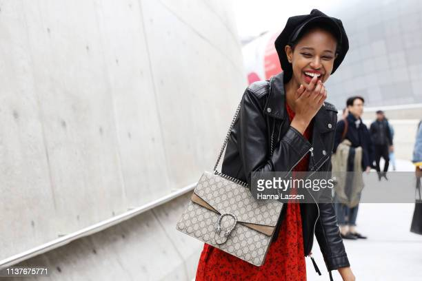 Guest wearing black hat leather rider jacket red dress and Gucci bag is seen at the Hera Seoul Fashion Week 2019 F/W at Dongdaemun Design Plaza at...