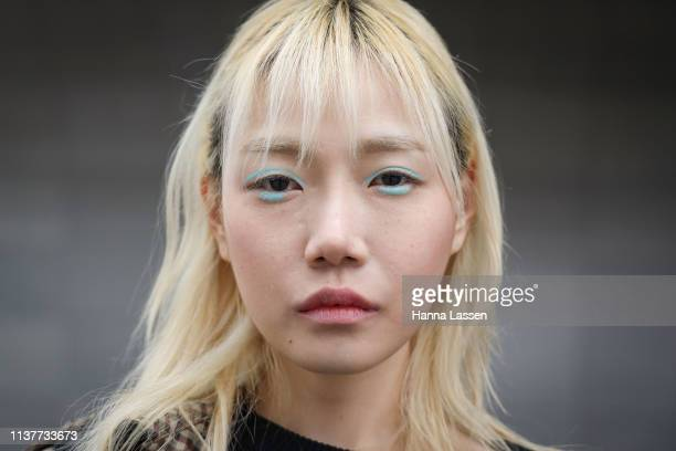 Guest wearing black jumper and check trench coat is seen at the Hera Seoul Fashion Week 2019 F/W at Dongdaemun Design Plaza at Dongdaemun Design...