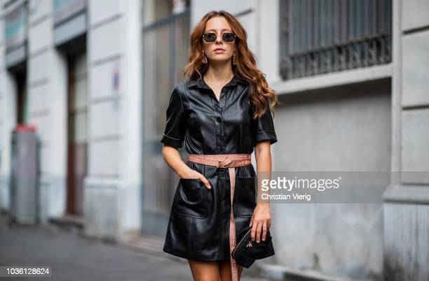 A guest wearing black leather dress Off White belt Prada clutch sunglasses black ankle boots is seen during Milan Fashion Week Spring/Summer 2019 on...