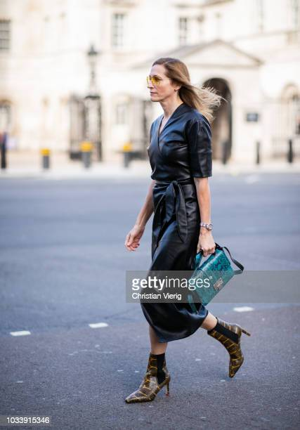 A guest wearing black leather dress snake print ankle boots is seen outside Anya Hindmarch during London Fashion Week September 2018 on September 15...