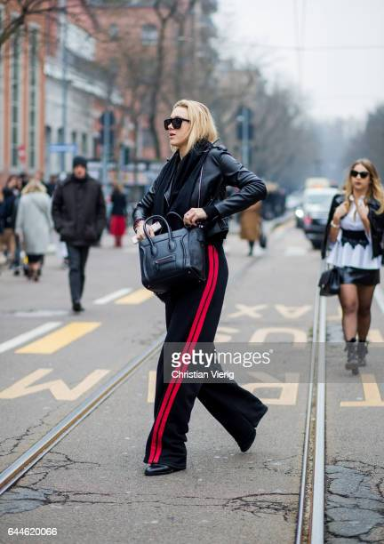 A guest wearing black leather jacket jogger pants with red stripes outside Fendi during Milan Fashion Week Fall/Winter 2017/18 on February 23 2017 in...