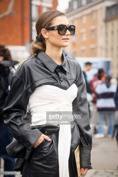 Guest wearing black leather shirt and white corset outside the Balmain show during the Paris Fashion Week Womenswear Fall/Winter on February 28, 2020...