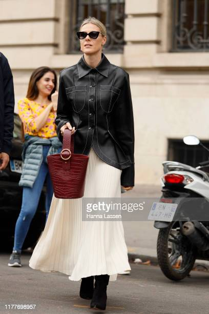 A guest wearing black leather shirt white pleated skirt and burgundy bag outside the Elie Saab show during Womenswear Spring/Summer 2020 show Paris...