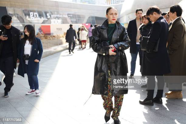 Guest wearing black leather trench coat mixed colour printed pants and black stiletto heels is seen at the Hera Seoul Fashion Week 2019 F/W at...