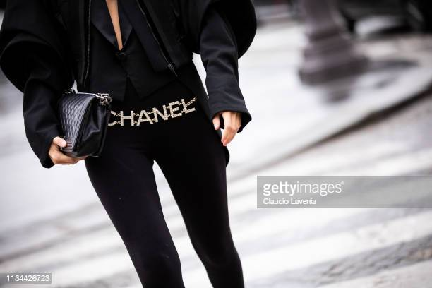 A guest wearing black leggings Chanel belt and black bag is seen outside Chanel on Day 9 Paris Fashion Week Autumn/Winter 2019/20 on March 5 2019 in...