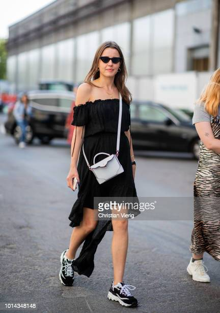 A guest wearing black off shoulder dress seen outside Ganni during the Copenhagen Fashion Week Spring/Summer 2019 on August 9 2018 in Copenhagen...