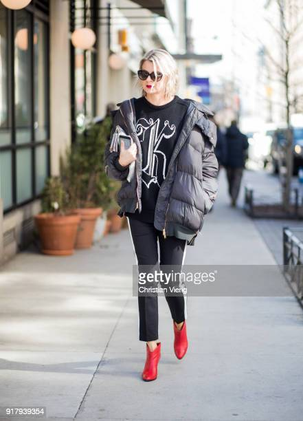A guest wearing black puffer jacket red ankle boots seen outside Gabriela Hearst on February 13 2018 in New York City