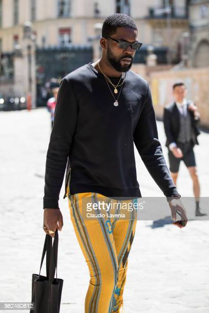 Guest, wearing black sweater and yellow pants, is seen in the streets of Paris before the Thom Browne show, during Paris Men's Fashion Week...