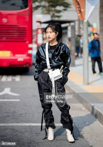 A guest wearing black vinyl jacket white bag black pants white ankle boots is seen at the Hera Seoul Fashion Week 2018 F/W at Dongdaemun Design Plaza...