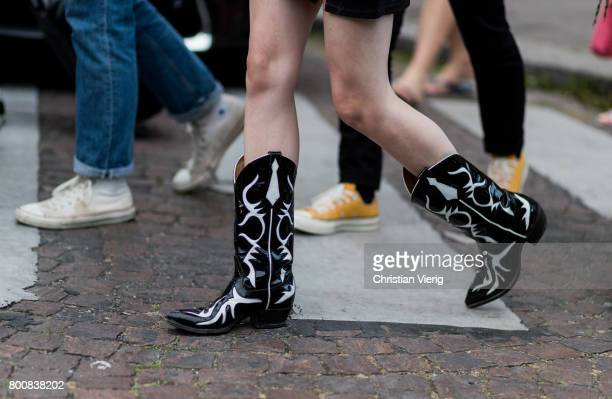 A guest wearing black white Cowboy boots outside Kenzo during Paris Fashion Week Menswear Spring/Summer 2018 Day Five on June 25 2017 in Paris France