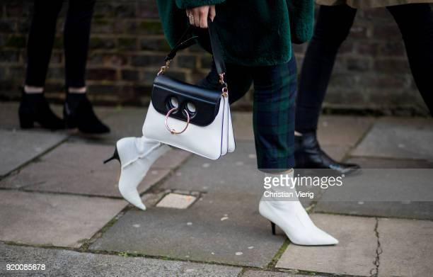 A guest wearing black white JW Anderson bag white ankle boots seen outside Temperley London during London Fashion Week February 2018 on February 18...