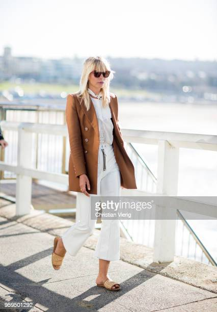 A guest wearing blazer jacket white cropped pants during MercedesBenz Fashion Week Resort 19 Collections at Icebergs Dining Room on May 17 2018 in...