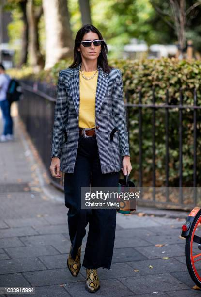 A guest wearing blue bag grey blazer is seen outside ALEXACHUNG during London Fashion Week September 2018 on September 15 2018 in London England