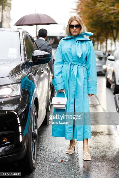 Guest wearing blue bow detailed trench and Balenciaga white clutch outside Lanvin on September 25, 2019 in Paris, France.